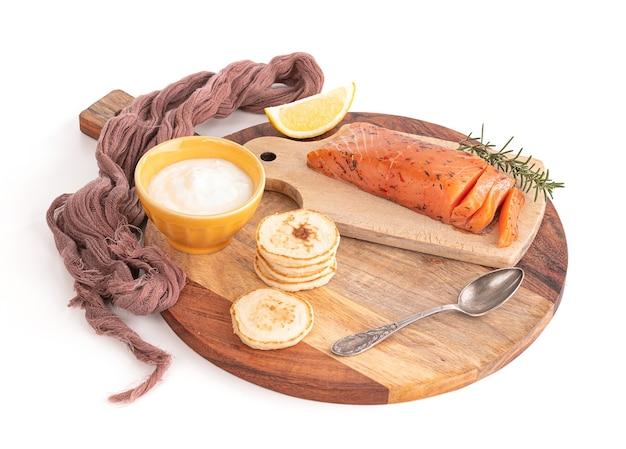 Salmone affumicato artigianale su tagliere con blinis e panna su sfondo bianco