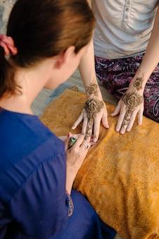Artista che applica un tatuaggio all'henné sulle mani delle donne. mehndi è l'arte decorativa indiana tradizionale. dal punto di vista dell'artista