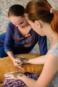 Artista che applica un tatuaggio all'henné sulle mani delle donne. mehndi è l'arte decorativa indiana tradizionale.