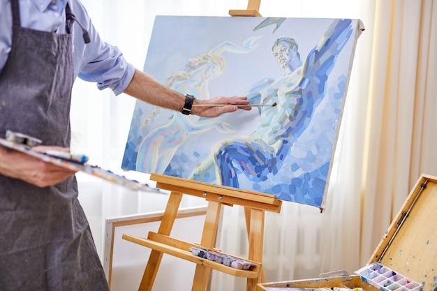 Artista che applica la pittura su tela con il pennello, la mente piena di immaginazione, pittore creativo durante il lavoro