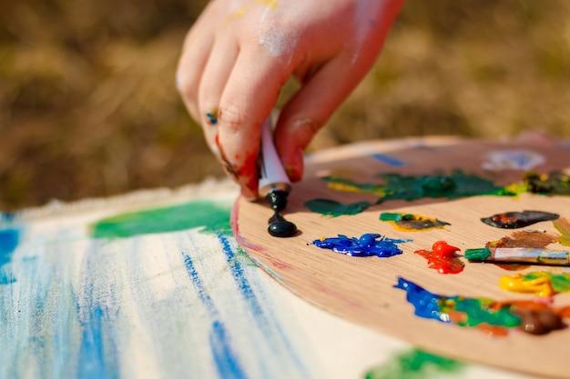 Mano dell'artista che disegna l'immagine e la tavolozza con colori e pennelli su sfondo di erba.