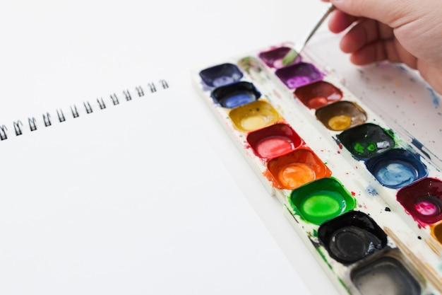 Mano dell'artista con colorante dell'acquerello e taccuino