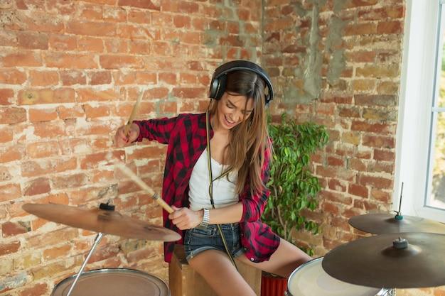 Artista. studio musicale domestico, bella donna che registra musica, canta e suona la batteria mentre è seduta sul posto di lavoro in soppalco oa casa. concetto di hobby, musica, arte e creazione. creazione del primo singolo.