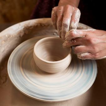 Artista che modella in argilla su un tornio da vasaio