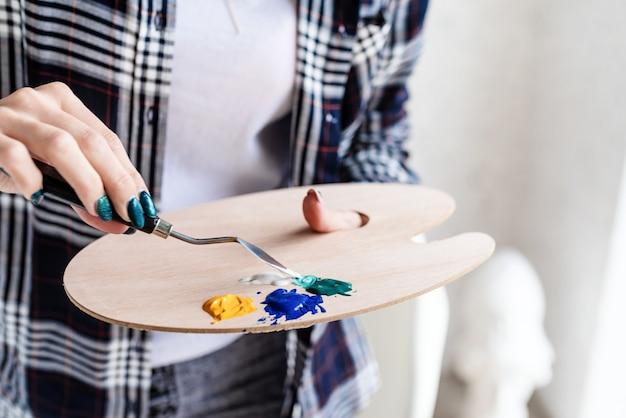 Tavolozza dell'artista. mani dell'artista mescolando le vernici sulla tavolozza. pittura a olio o acrilica. messa a fuoco selettiva