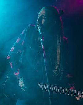 Artista che suona la chitarra e sente i testi