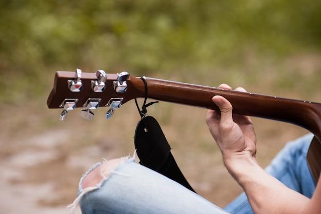 Artista che suona la chitarra nella foresta. bard escursionismo e stile di vita del viaggiatore