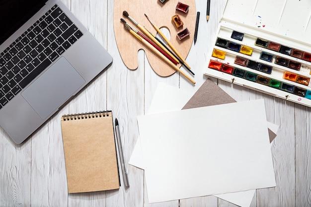 Acquerelli sul posto di lavoro dell'artista, tavolozza, blocco per schizzi di pennelli e laptop