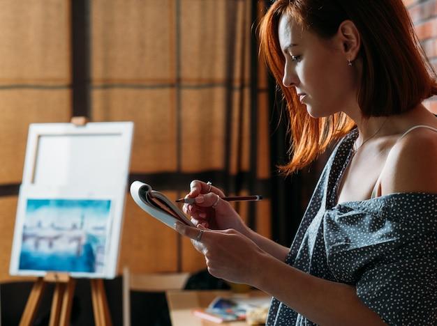 Schizzo dell'artista. area di lavoro di studio. redhead pittore disegno schizzo a matita con cavalletto