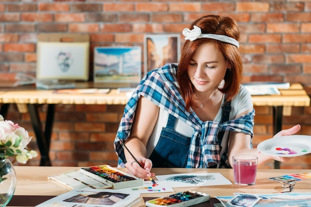 Artista al lavoro. pittura ad acquerello. pittore femminile della testarossa che mescola i colori. schizzi e forniture di tavolozze in giro.