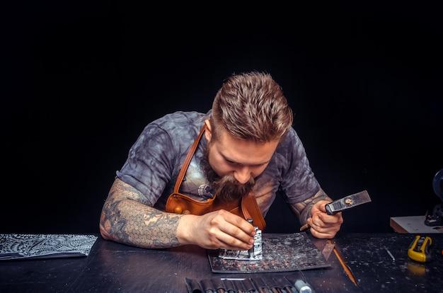 Artista che lavora con la pelle creando un nuovo prodotto in pelle nella conceria.