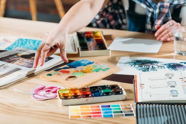 Luogo di lavoro dell'artista. ispirazione. pittore che crea opere d'arte con album da disegno e forniture di tavolozza in giro.