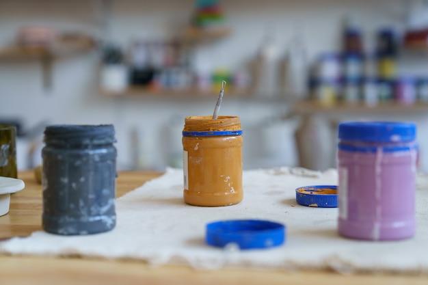 Barattoli aperti sul posto di lavoro dell'artista con vernice per decorare l'artigianato della ceramica sul tavolo nel tempo libero dell'arte dell'officina