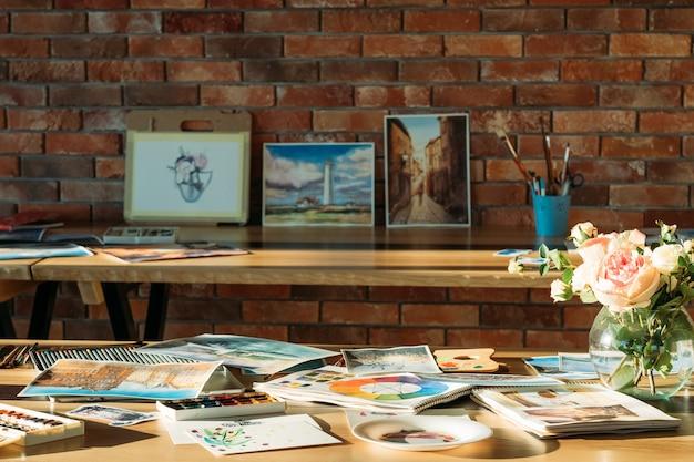 Luogo di lavoro dell'artista. atmosfera da studio del pittore. opere d'arte ad acquerello e forniture d'arte in giro.