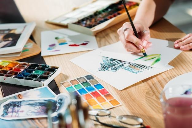 Luogo di lavoro dell'artista. creazione di pittura ad acquerello. mano che fa pennellate di colore con schizzi e forniture di tavolozza intorno.