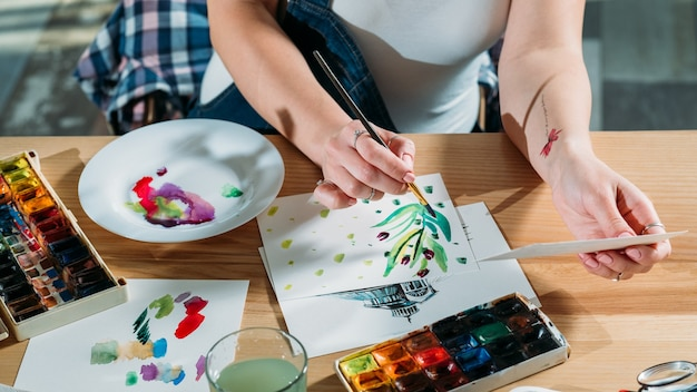 Luogo di lavoro dell'artista con bozze e forniture di tavolozza in giro. pittore che fa le pennellate di schizzo ottenendo ispirazione.