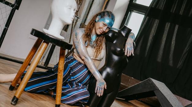 Artista in officina. donna con scintillii blu sul viso. il concetto di freaks e persone creative. le persone sono diverse dalle altre. individualità
