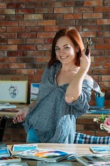 Area di lavoro dell'artista. atmosfera creativa. attraente donna rossa in posa con i pennelli
