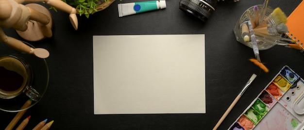 Area di lavoro dell'artista con carta da disegno e strumenti di pittura sulla scrivania nera