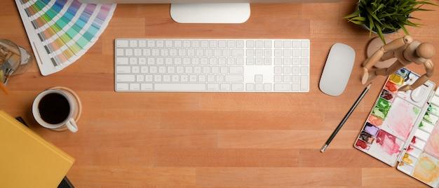 Tavolo da lavoro dell'artista con computer, strumenti di pittura, forniture, decorazioni e copia spazio sul tavolo di legno