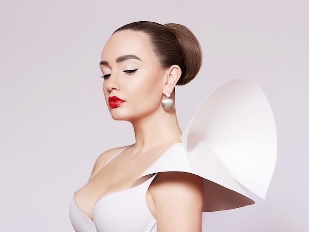 Ritratto artistico di una donna bella ed elegante in un abito bianco. stile elegante. un modello alla moda in gioielli d'oro.