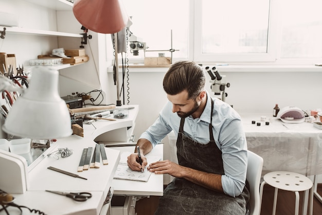 Abilità artistiche. il giovane gioielliere barbuto sta disegnando uno schizzo nel suo laboratorio