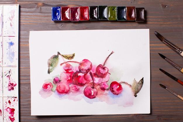 Opera d'arte, ciliegie di pittura ad acquerello con strumenti di disegno su un tavolo di legno
