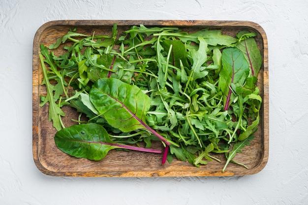 Rucola, bietole mix di erbe insieme, su pietra bianca sullo sfondo, vista dall'alto laici piatta