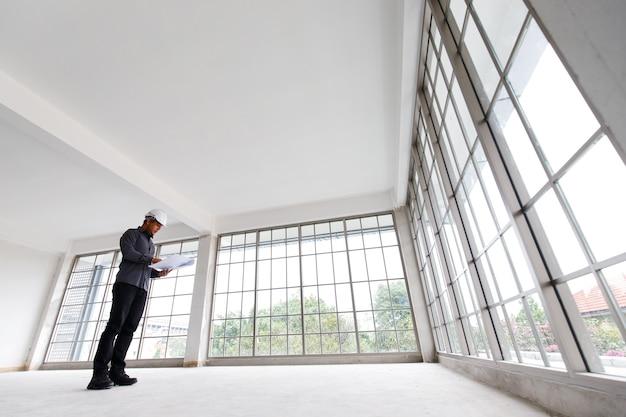 L'ingegnere di asain in casco bianco con stampa blu sta controllando la stanza della costruzione
