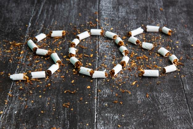 La cenere e la sigaretta sembrano una croce, un concetto artistico per la giornata mondiale senza tabacco. segno sos di tabacco. rischi per la salute della nicotina. la sigaretta uccide. foto scura in bianco e nero