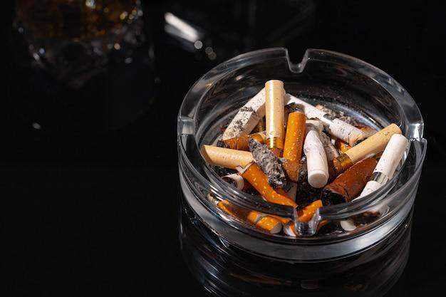 Posacenere pieno di mozziconi di sigaretta su sfondo nero si chiuda