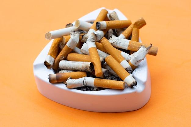 Posacenere e sigarette sulla superficie arancione