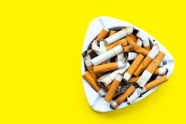 Posacenere e sigarette su sfondo giallo. copia spazio