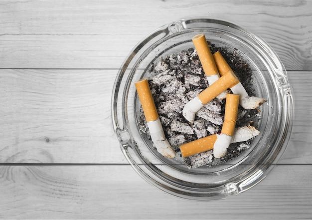 Posacenere e sigarette fumate su sfondo
