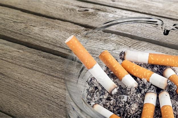Posacenere e sigarette fumate su fondo in legno