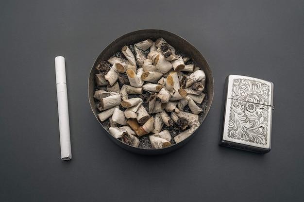 Posacenere con mozziconi di sigaretta sullo sfondo di un tavolo grigio. una sigaretta nuova e un accendino a benzina nelle vicinanze.