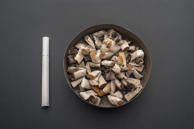 Posacenere con mozziconi di sigaretta sullo sfondo di un tavolo grigio. una nuova sigaretta è vicina.