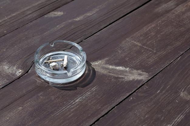 Posacenere con mozziconi di sigaretta su tavola di legno fumo passivo
