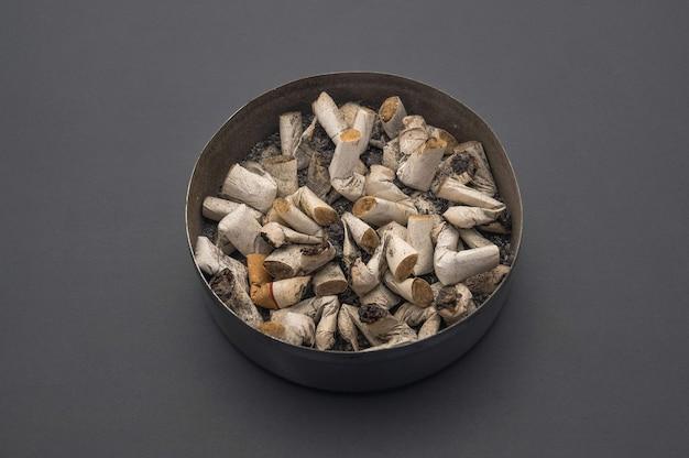Posacenere con coperchio e mozziconi di sigaretta sullo sfondo di un tavolo grigio