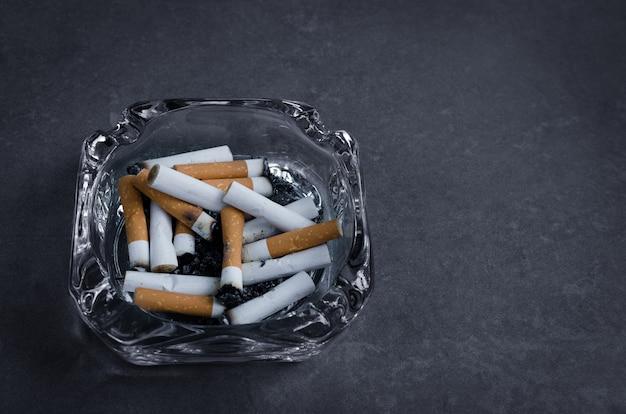 Posacenere con molte sigarette che i fumatori possono fumare solo nell'area fumatori limite, smettere di fumare. uscire dal concetto di dipendenza.