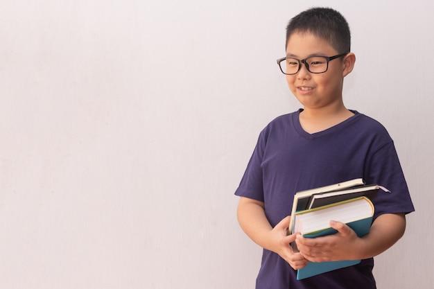 Libri della tenuta del ragazzo dell'asia pronti per la scuola