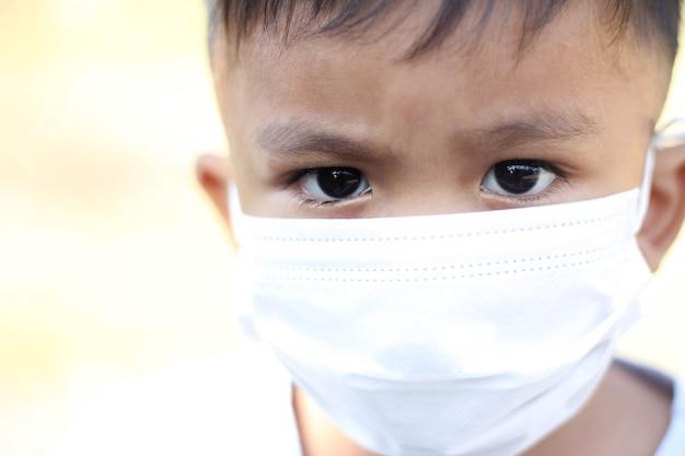 Ragazzo asiatico che indossa una maschera facciale per proteggere il virus corona e l'inquinamento atmosferico pm2.5 con sfondo sfocato.