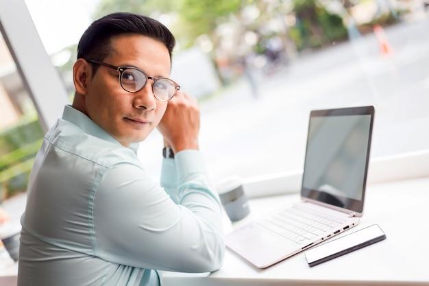 Uomo di affari dell'asia che lavora con il computer portatile mentre sedendosi caffetteria. concetto dei giovani di affari