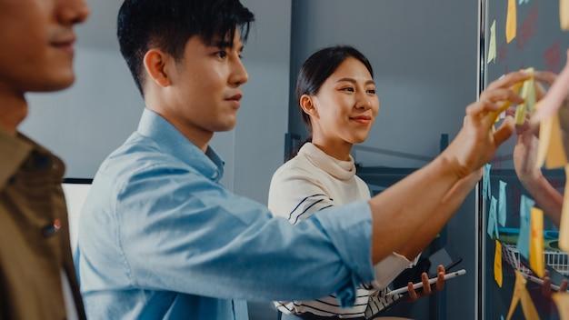 Gli uomini d'affari asiatici stanno dietro la parete di vetro trasparente ascoltano il manager che indica il progresso del lavoro
