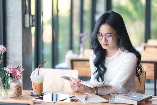 Ragazza dell'asia che legge un libro al caffè