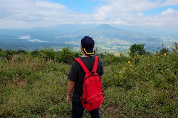 L'uomo dell'asia si leva in piedi in su davanti alla vista della montagna in tailandia