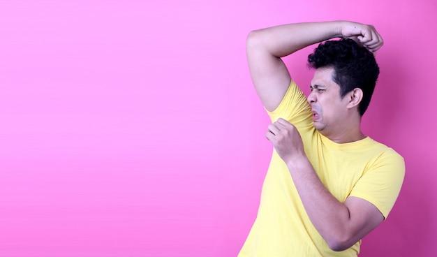 Uomo dell'asia che suda eccessivamente odorando cattivo isolato su fondo rosa in studio