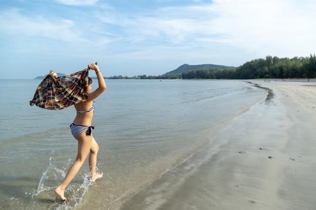 Le ragazze adolescenti dell'asia che portano il bikini che funzionano alla spiaggia dal fondo del mare è un cielo blu.