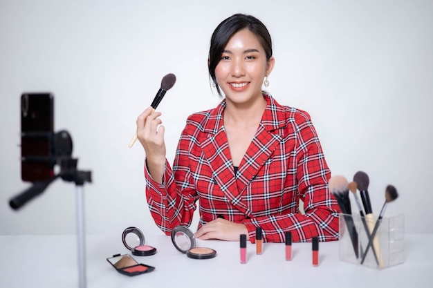 La blogger di bellezza donna asiatica fa trucco, recensisce prodotti di bellezza per video blog