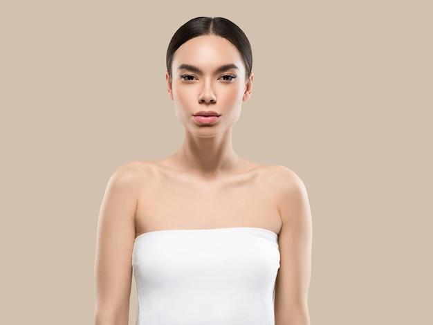 Ritratto del corpo del viso di bellezza della donna dell'asia che tocca la sua pelle sana del viso. colore di sfondo. marrone